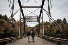 Couple Walking on Gray Bridge at Daytime Royalty Free Stock Image