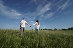 Couple walking through green field Stock Images