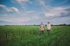 Couple walking through green field Stock Photo