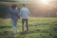 Couple walking on green hill in warm summer evening stock photography
