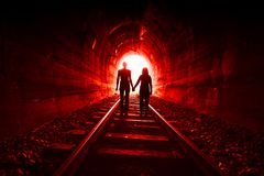 Couple walking together through a railway tunnel Royalty Free Stock Photos