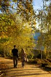 Couple walking hand in hand in autumn. Couple walking hand in hand along park path with early autumn tress and a blue sky stock image