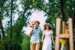 Couple walking happily among the trees, looking down stock image