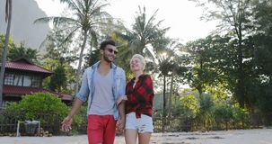 Couple Walking Hold Hands Talking Happy Man And Woman In Tropical Palm Tree Park Communication. Slow Motion 60 stock footage