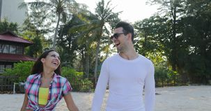 Couple Walking Hold Hands Talking Happy Man And Woman In Tropical Palm Tree Park Communication. Slow Motion 60 stock video footage