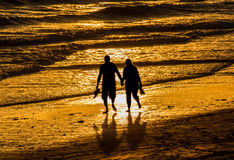 Couple walking holding hands beach. Silhouette couple walking at sunset on the beach holding hands. Love, romance, valentines concept