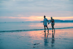 Couple Walking Holding Hands On Beach At Sunset, Young Tourist Man And Woman On Sea Holiday stock photography