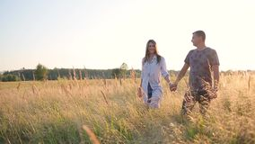 Couple walking holding hands in the grass field stock video footage