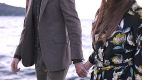 Couple walking holding hands near the sea stock footage