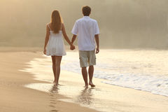 Couple walking and holding hands on the sand of a beach. Back view of a couple walking and holding hands on the sand of a beach at sunset Royalty Free Stock Photos