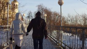 Couple walking holding hands on a small bridge full of love locks. 4K steadicam shot stock video footage