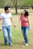 Couple walking holding hands and smiling Royalty Free Stock Image