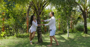 Couple Walking Holding Hands In Tropical Garden Embracing And Kissing, Happy Man And Woman Outdoors. Slow Motion 60 stock video footage