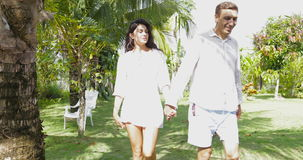 Couple Walking Holding Hands In Tropical Garden Talking, Happy Man And Woman Outdoors. Slow Motion 60 stock footage