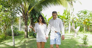 Couple Walking Holding Hands In Tropical Garden Talking, Happy Man And Woman Outdoors. Slow Motion 60 stock video footage