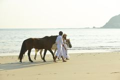 A couple walking horses on beach Stock Photography