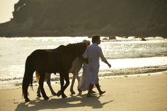 A couple walking horses on beach Stock Photo