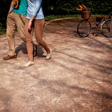 Couple walking and hugging in the park with bicycle on the backg Stock Photography
