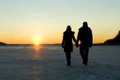 Couple walking on ice at sunset. Holding hands Stock Photos
