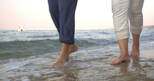 Couple Walking in Incoming Sea Waves. Steadicam shot of bare feet of two people walking along the sea in incoming waves stock footage