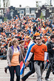Couple walking at Koninginnedag 2013. Koninginnedag or Queens Day was a national holiday in the Kingdom of the Netherlands until 2013. Celebrated on 30 April ( Stock Photo