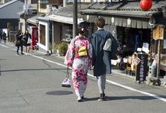 Couple walking in Kyoto street. Woman and man, wearing traditional Japanese kimono, walking in a hidden and old street in Kyoto, Japan Royalty Free Stock Image