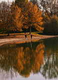 Couple walking on lake border with red trees reflection on water Stock Photography