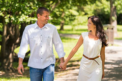 Couple walking and laughing in a park Stock Photography