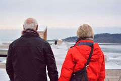 Couple walking on a long pier, on a cold winter day. Royalty Free Stock Photography