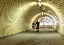 Couple walking in a long tunnel Royalty Free Stock Image