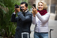Couple walking with luggage, camera and smartphone Royalty Free Stock Photo
