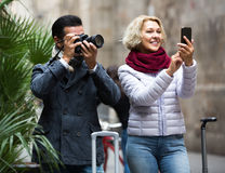 Couple walking with luggage, camera and smartphone Royalty Free Stock Images