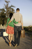 Couple walking with luggage in hand Royalty Free Stock Images
