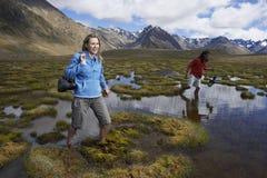Couple Walking Through Mountain Pond Stock Photography