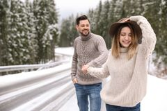 Couple walking near snowy forest, space for text royalty free stock photography