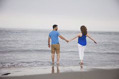 Couple walking into ocean Royalty Free Stock Images