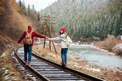 Couple walking on old railroad in mountains. Young couple walking together on old railroad in mountains Royalty Free Stock Photos