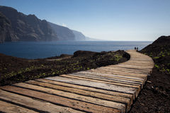 Free Couple Walking On Wooden Path To Ocean Royalty Free Stock Photo - 63477365