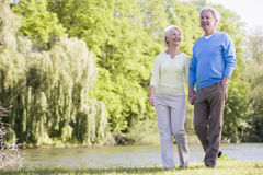 Couple Walking Outdoors At Park By Lake Smiling Stock Photo