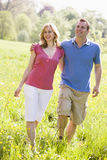 Couple walking outdoors holding flower smiling