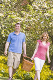 Couple walking outdoors with picnic basket smiling Stock Photography