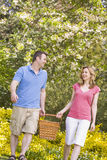 Couple walking outdoors with picnic basket smiling Royalty Free Stock Photos