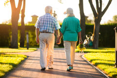 Couple walking on park alley. Back view of elderly people. Strong ties of love. I'm with you royalty free stock photo