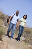 Couple walking on path holding hands and smiling Stock Image