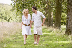 Couple walking on path holding hands smiling Royalty Free Stock Image