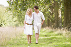 Couple walking on path smiling Stock Photography
