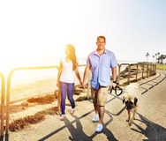 Couple walking pet dog by the ocean Royalty Free Stock Images