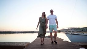 Couple walking on the pier in harbour. Slow motion steadicam shot of young man and woman holding hands and walking along the pier in the harbour at sunset stock footage