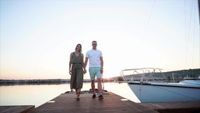 Couple walking on the pier in harbour. Slow motion steadicam shot of young man and woman holding hands and walking along the pier in the harbour at sunset stock video