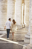 Couple Walking Between Pillars Royalty Free Stock Photography